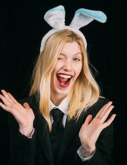 イースターの女性。ウインクバニー耳の幸せな女性の肖像画。まばたきイースターバニーの女の子の顔のクローズアップ。ウィンクを与える。面白いイースター