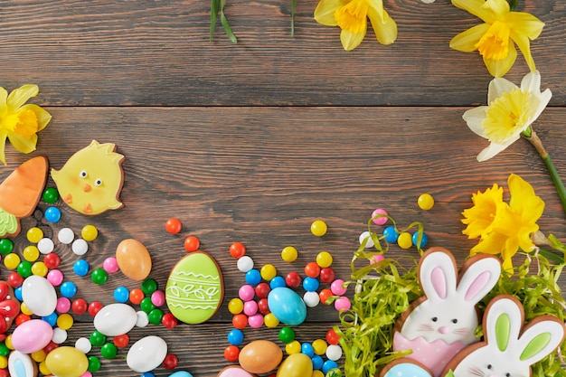 Easter wooden background with daffodils and cookies