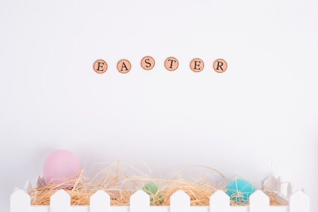 Easter word near bright eggs between hay in box