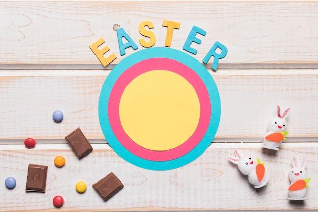 ウサギと丸い紙フレームにイースターの言葉。チョコレートのかけらと木製の背景上の宝石
