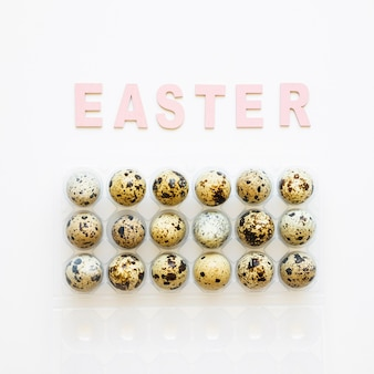 Easter word and quail eggs in rack