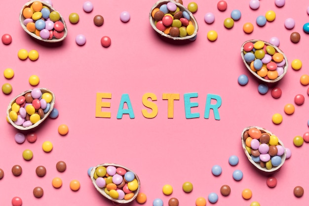 Easter word surrounded with colorful gem candies and easter eggs on pink background