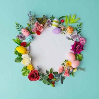 화려한 봄 꽃, 잎 및 부활절 달걀으로 만든 부활절 화 환. 종이 카드와 함께 자연 라운드 프레임 레이아웃.
