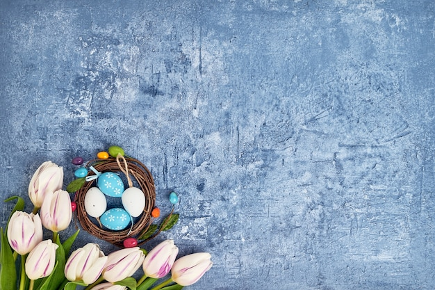 Easter wreath, white tulips and decorative easter eggs on blue wall. top view, copy space