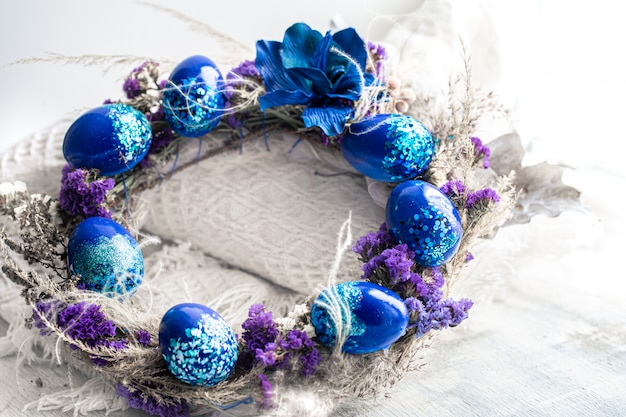 Easter wreath with blue eggs with sequins at the window.