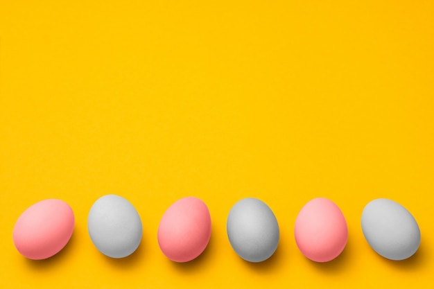 Easter yellow background with copy space. pink and white eggs in a row at bottom