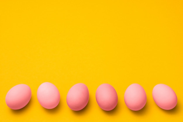 Easter yellow background with a row of pink colored eggs with copy space on top