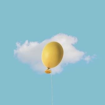 Пасхальный желтый яйцо воздушный шар с белым облаком на голубом небе.