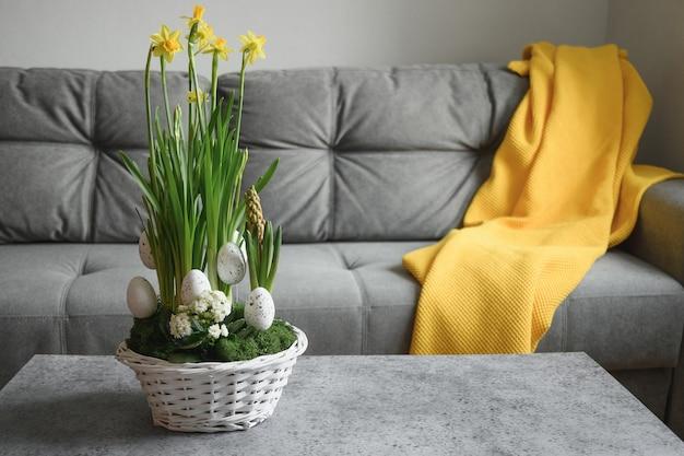 リビング ルームにグレーのソファを備えたホーム インテリアのイースター イエローの花の構成。家庭生活。美しい diy の花の構成。