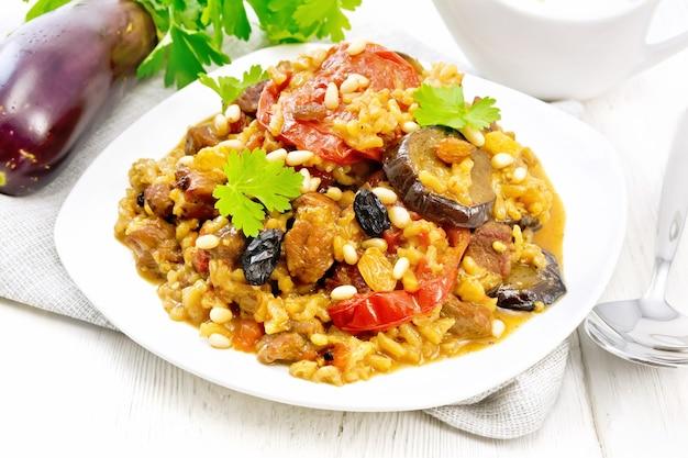 Восточно-европейское национальное блюдо маклубе из риса, баклажанов, помидоров, специй и чеснока в тарелке на полотенце на фоне светлой деревянной доски