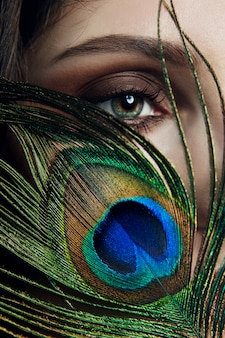 Eastern arab woman with a peacock feather in her hands near her face. beauty fashion makeup arab women, big beautiful eyes. beautiful smooth skin, peacock feather near eyes