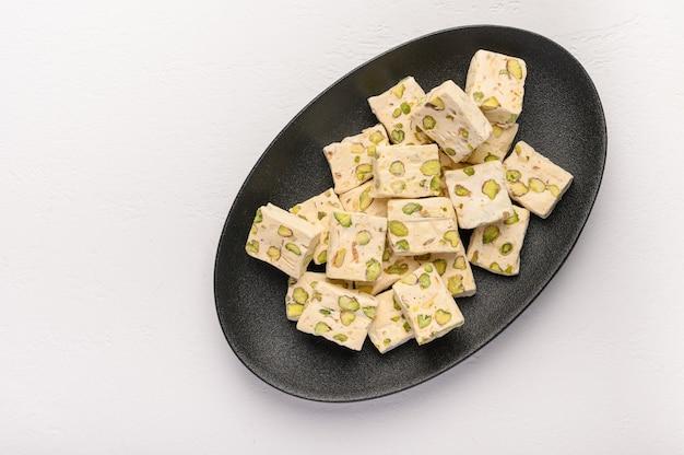 밝은 배경에 세라믹 접시에 피스타치오와 동부 아랍 누가 단맛.