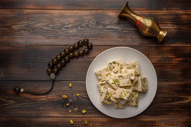 나무 배경에 흰색 세라믹 접시에 피스타치오와 동부 아랍 누가 단맛.