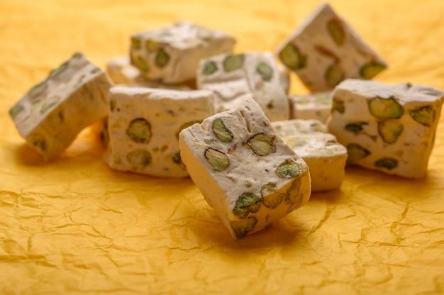 노란 종이 배경에 피스타치오와 동부 아랍 누가 단맛.