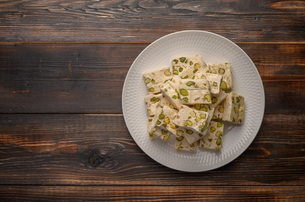 Eastern arabic nougat sweetness with pistachios on a white ceramic plate on a wooden background.