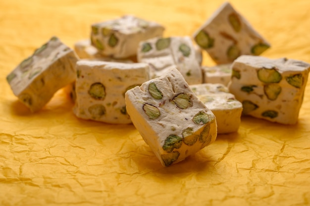 Eastern arabic nougat sweetness with pistachios on yellow paper background.
