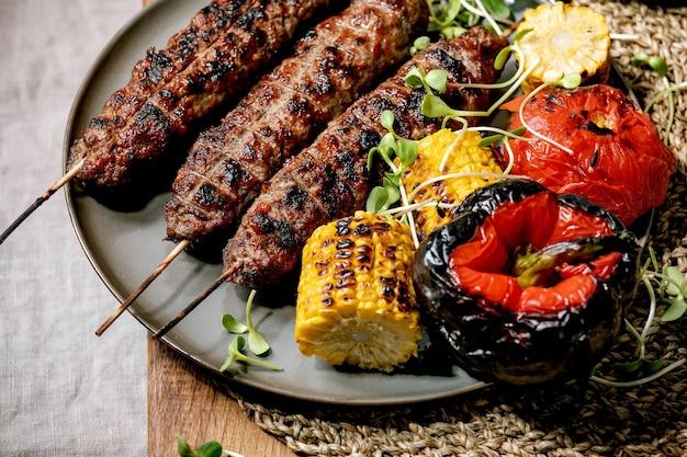 Восточный фастфуд. жареный на гриле острая говядина люля кебаб на палочках на лепешке с жареными овощами в початках сладкой кукурузы, помидорами и паприкой, томатным соусом на деревянном столе.