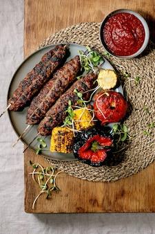 Восточный фастфуд. жареный пряный говядина люля кебаб на палочках на тарелке с жареными овощами в початках сладкой кукурузы, помидорами и перцем, томатным соусом на деревянном столе. плоская планировка