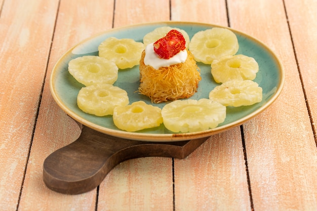 Eastern pastry cookies inside plate with white cream dried pineapple rings on wooden table