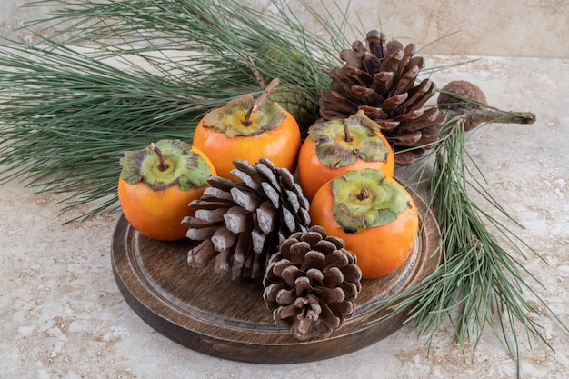 Eastern persimmons and conifer cones bundle together on marble surface.