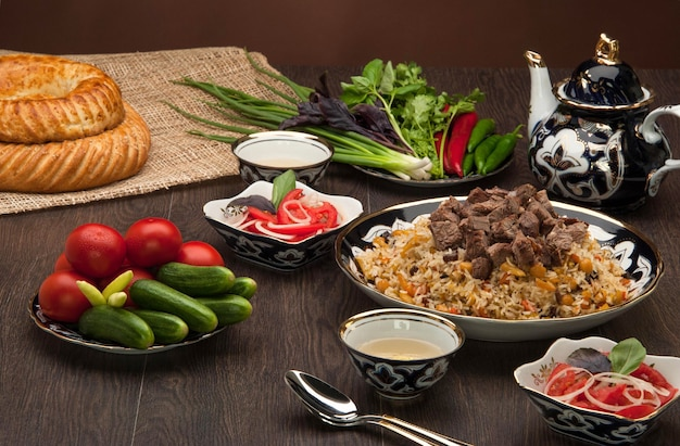 Eastern pilaf and salads with fresh vegetables, and cake and tea on a wooden board