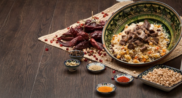 Eastern pilaf with spices and dried chilli on a wooden board