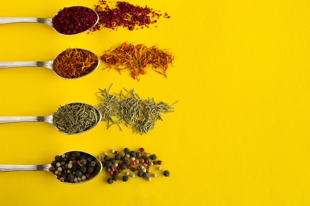 Eastern spices in the silver spoons on yellow. top view.