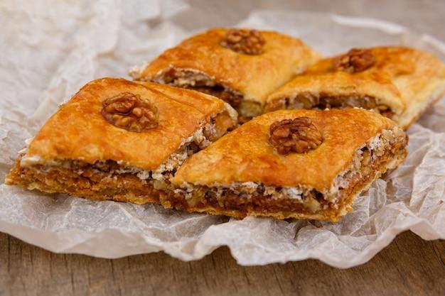 ベーキングペーパーの上にクルミで飾られた東部のお菓子、バクラヴァデザート
