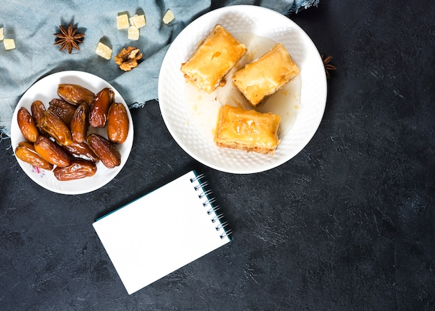 Eastern sweets with dates fruit and notepad
