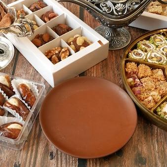 ナッツ、キャンディー、木製の背景に日付と東洋のお菓子