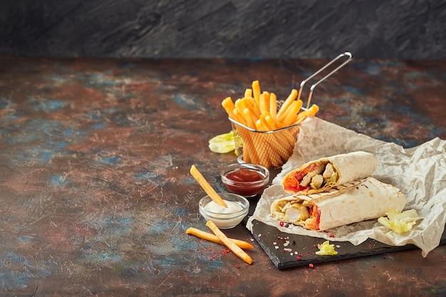 Восточная традиционная шаурма с курицей и овощами и картофелем фри с соусами на грифеле. быстрое питание. восточная еда.