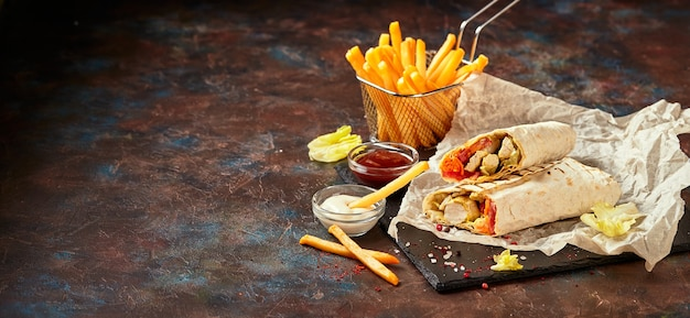 Восточная традиционная шаурма с курицей и овощами и картофелем фри с соусами