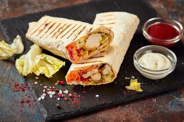 Восточная традиционная шаурма с курицей и овощами, донер кебаб с соусами на грифеле. быстрое питание. восточная еда.