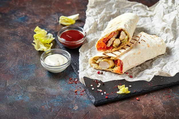 닭고기와 야채를 곁들인 동부 전통 샤와 마, 슬레이트에 소스를 얹은 도네 르 케밥. 패스트 푸드. 동부 음식.