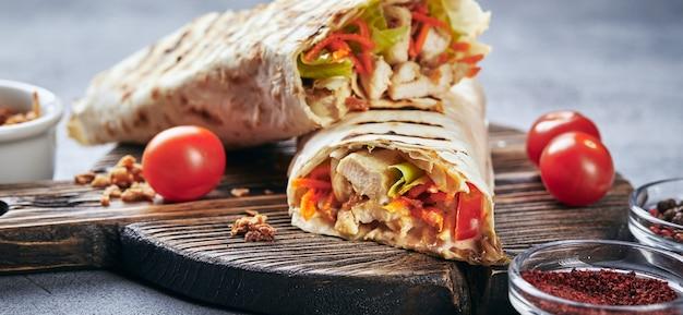 닭고기와 야채를 곁들인 동부 전통 shawarma, 나무 커팅 보드에 소스를 곁들인 doner kebab. 패스트 푸드. 동부 음식.