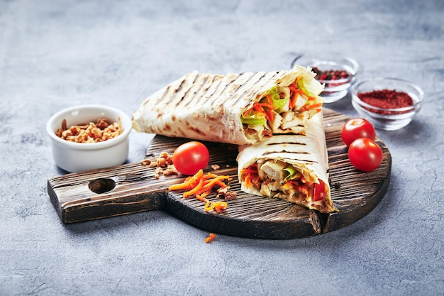 Eastern traditional shawarma with chicken and vegetables, doner kebab with sauces on wooden cutting board. fast food. eastern food.