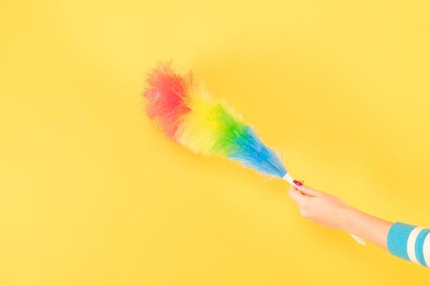 簡単なホコリ掃除。はたきを持つ女性の手。黄色の背景にスペースをコピーします。