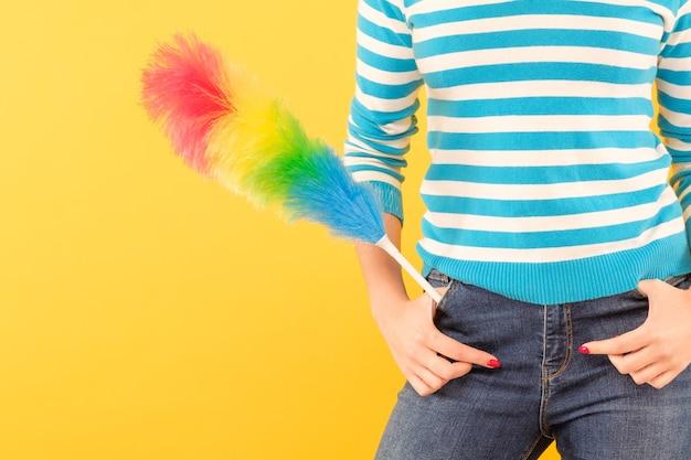 簡単なホコリ掃除。ポケットに羽ばたきを持つ女性。黄色の壁にスペースをコピーします。