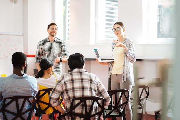 쉬운 설명. 영리한 경험이 풍부한 젊은 기업가가 손에 노트북을 들고 청중 앞에 서서 자신의 성장에 대해 이야기합니다.
