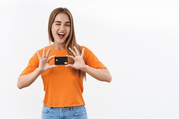 オレンジ色のtシャツで気楽な幸せなブロンドの女の子