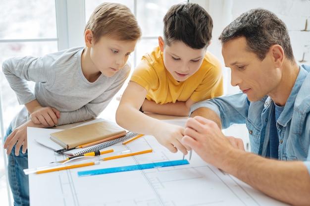 簡単なレッスン。父親のワークデスクに寄りかかって、父親がコンパスの使い方を教えている間、コンパスの使い方を学んでいる好奇心旺盛な10代前の男の子