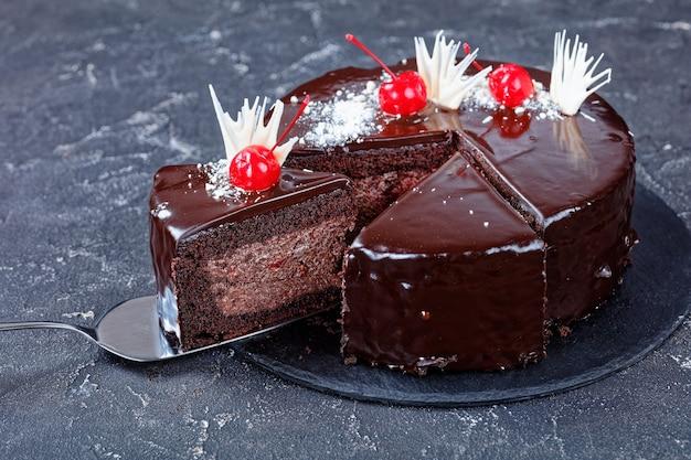 缶詰のチェリーで飾られた上にダークチョコレートの釉薬を詰めたチェリーパイの簡単な有機湿ったチョコレートブラウニーケーキ