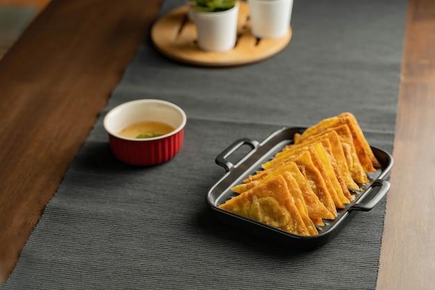 Легкий рецепт, закуски, жареные вонтоны с начинкой из свинины в черном блюде на серой подставке для посуды, коричневый деревянный стол подается со сладким сливовым соусом в красной миске