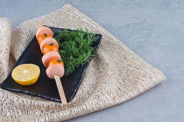 Легкая закуска готова к употреблению. колбаса и помидор.