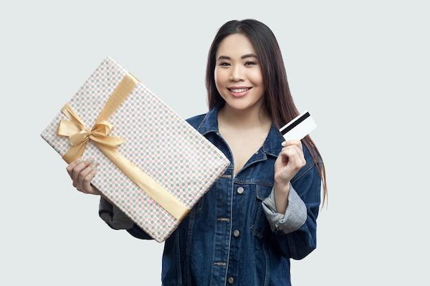 Легко купить в интернет-магазинах. удовлетворенная молодая азиатская девушка в голубой джинсовой куртке стоя и держа настоящий момент с желтым бантом и банковской картой, смотря камеру. изолированные, студийный снимок, серый фон