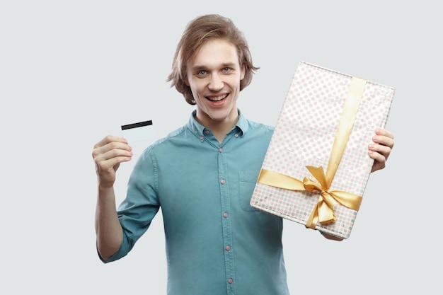 Легко купить в интернет-магазинах! удовлетворенный молодой человек в голубой рубашке стоит и держит подарок с желтым бантом и банковской картой, глядя в камеру. крытый, изолированный, студийный снимок, серый фон