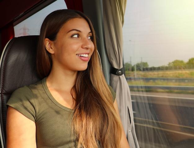 Легкие путешествия. девушка-путешественница, используя удобный автобус для перемещения. молодая красивая женщина, глядя через окно автобуса. счастливый пассажир автобуса, путешествующий сидя в кресле и глядя в окно.