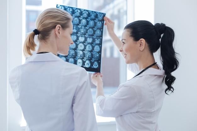 뇌 x 선 이미지를 검사하고 논의하는 동안 뢴트겐 캐비닛에서 일하는 느긋한 웃는 젊은 간호사