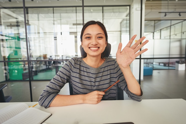 Easygoing woman sitting at table and waving her hand