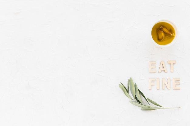 Mangiare testo fine con ramoscello di ulivo e olio di spicchio d'aglio in una ciotola su sfondo bianco